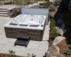 Hot tub installed in a backyard on a patio.