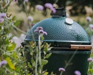 The Big Green Egg surrounded by flowers and greenery.