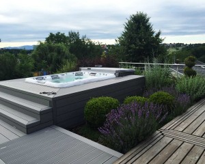 Sundance Spas hot tub installed in the ground in a backyard space.