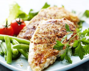 Healthy grilled chicken served on a place with vegetables.