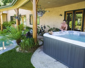 Woman soaking in her outdoor hot tub and talking to her husband.
