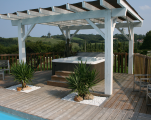 Outdoor hot tub installed on a patio underneath a pergola on a bright, sunny day.